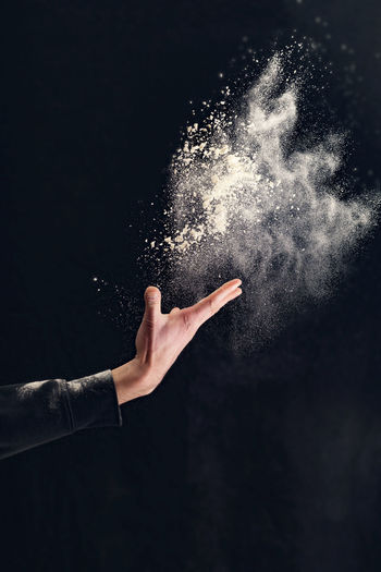 Close-up of hand throwing talcum powder against black background