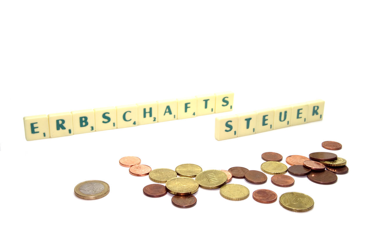 Coins And Scrabble Letters On White