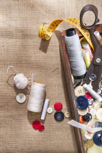 Directly above view of various sewing items on jute