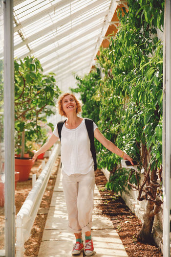 Blonde Casual Clothing Culry Curly Hair Front View Full Length Girl Green Color Greenhouse Growth Lifestyles Outdoors Person Plant Plants Plants And Flowers Portrait Smiling Standing Summer Original Experiences Natural Light Portrait People And Places Connected By Travel