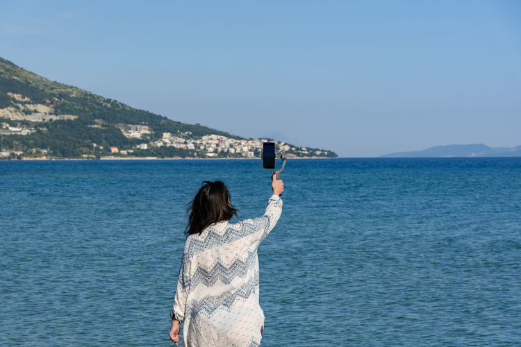 Rear view of woman photographing sea against clear sky
