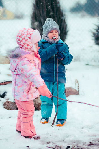 Little girl and boy enjoying marshmallows prepared over campfire outdoors in the winter. Children holding wooden sticks with toasted candies. Kids wearing warm clothes Winter Child Outdoors Childhood Boy Girl Cold Enjoyment Enjoy Kid Children Wintery Winter Snow Snowing Picnic Family Eating Campfire Roasting Marshmallows Snack Roasted Spending Time