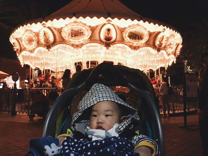 Baby In Carriage Against Carousel At Amusement Park During Night