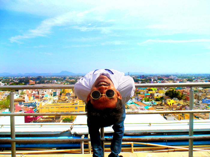 Young man bending over backwards with city in background against sky