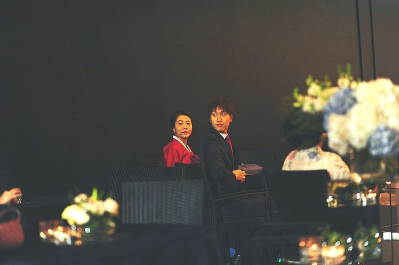 Couple sitting on chairs during wedding ceremony