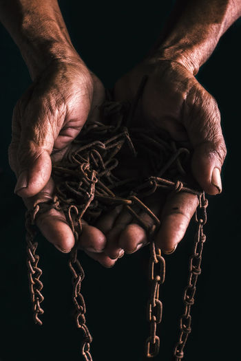 Cropped Hands Of Man Holding Chain Against Black Background