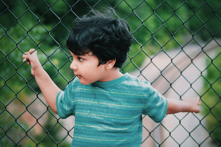 kid in thoughts Blue Casual Clothing Chainlink Fence Child Cute Day Focus On Foreground Kid Leisure Activity Lifestyles Looking Away Looking Away From Camera Portrait Thoughtful Thoughtfulness Thoughts
