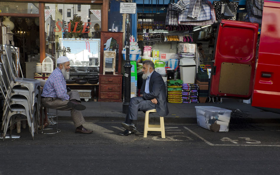 Two men having a conversation in Portobello Road on 30th of June 2018 in London, United Kingdom. Portobello Road in Notting Hill is a hub for the Caribbean and the North African communities. The result is that this side of the Royal Borough of Kensington and Chelsea is very lively with diverse ethnic groups living closely. (photo by Lorenzo Grifantini) Diversity London Portobello Road Business Chair English Lifestyles Market Multicultural Occupation Real People Two People