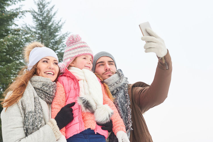 Man Taking Selfie With Family Against Sky During Winter