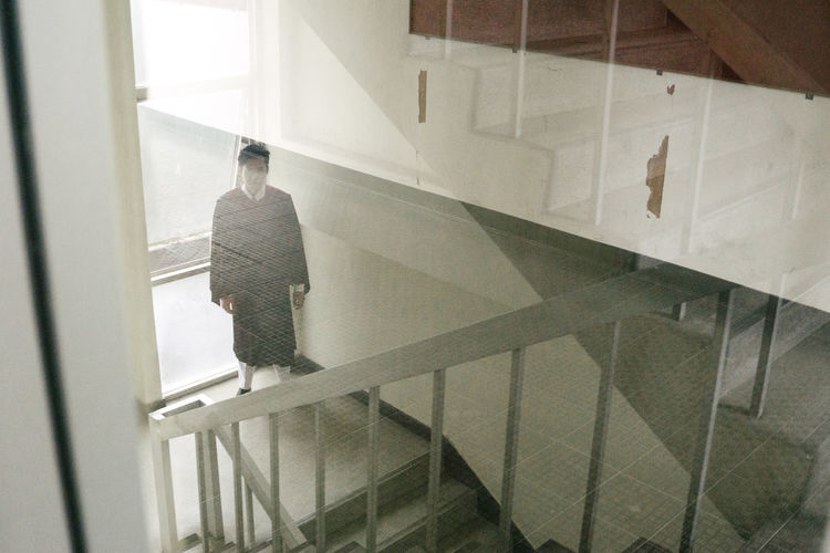Portrait Of Man In Graduation Gown Standing On Stairs In Building