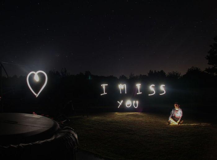 Man sitting on field by illuminated text at night