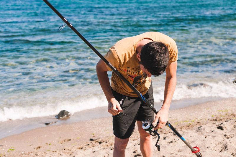 Full length of man fishing on beach