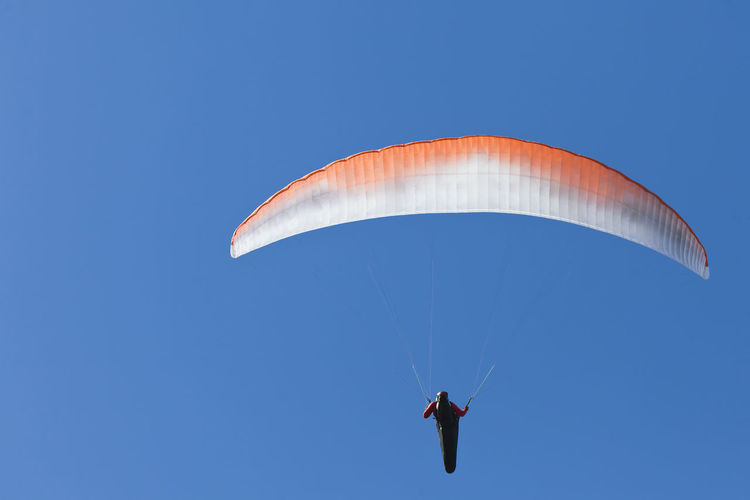 Low angle view of person paragliding against clear blue sky during sunny day