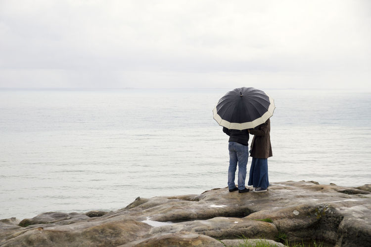 Rear View Of Couple With Umbrella