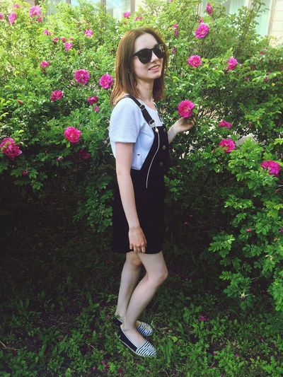 Portrait Of Young Woman Standing By Plants