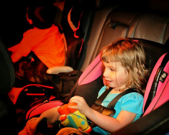 Girl looking away while sitting on baby seat in car