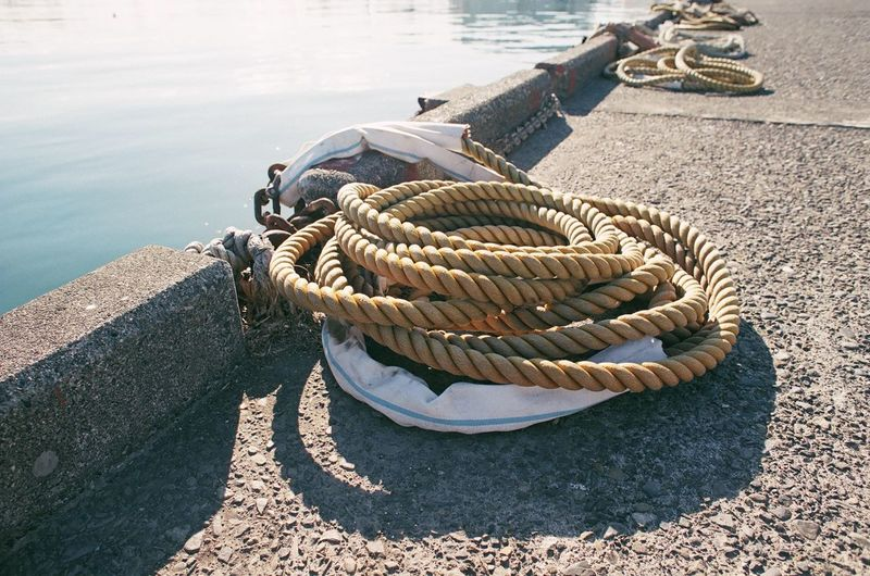High angle view of rope tied to bollard at harbor
