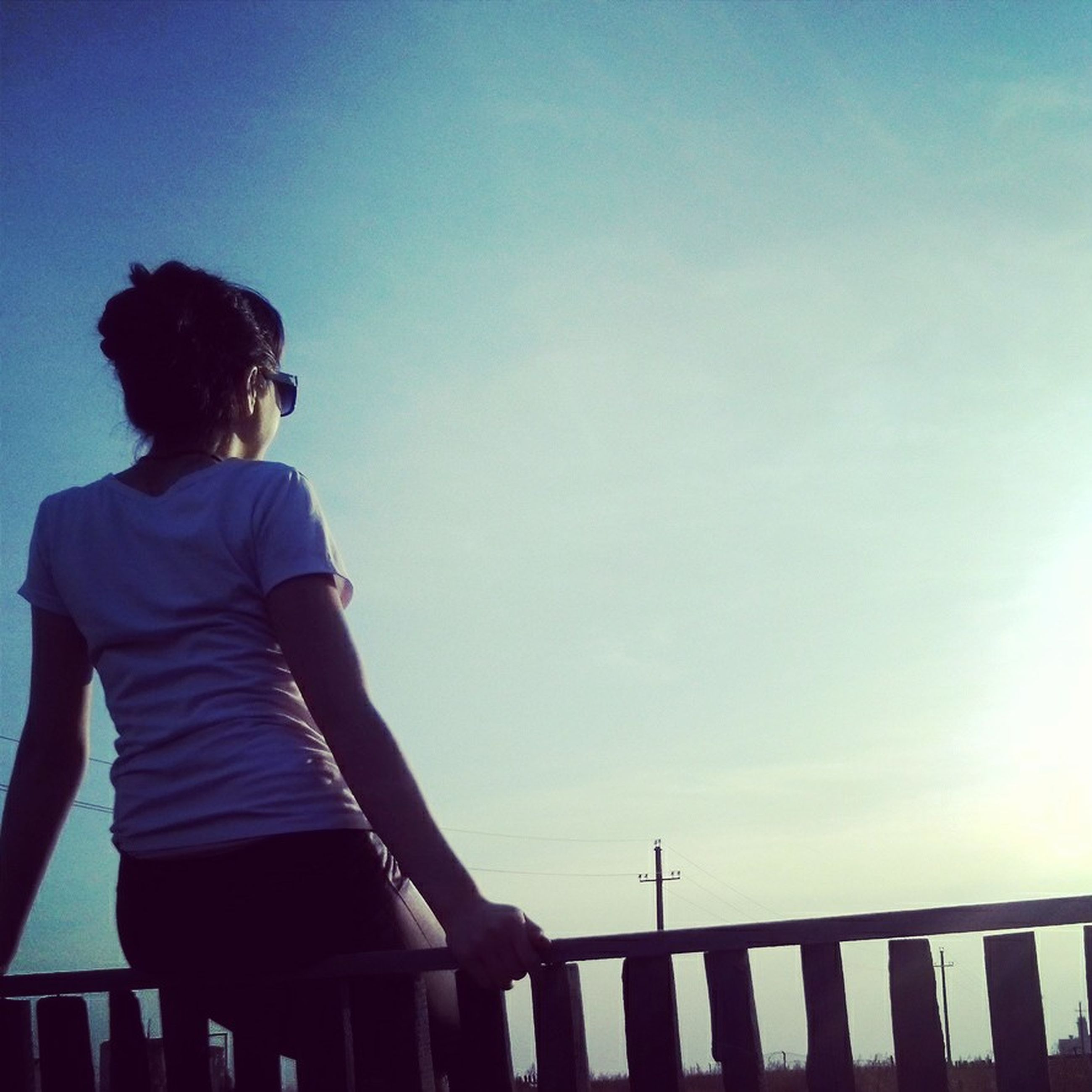 lifestyles, leisure activity, standing, railing, three quarter length, sky, casual clothing, rear view, clear sky, full length, copy space, silhouette, waist up, sitting, looking at view, person, relaxation, blue
