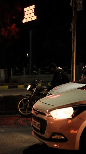 Mode Of Transportation Transportation Land Vehicle Car Night City Motor Vehicle Architecture Street Illuminated One Person Real People Building Exterior Built Structure Lighting Equipment Incidental People Motorcycle Focus On Foreground Outdoors Road Crash Helmet