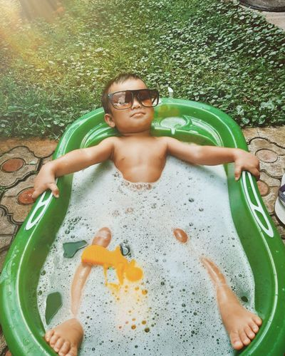 High angle view of shirtless boy relaxing in bathtub outdoors