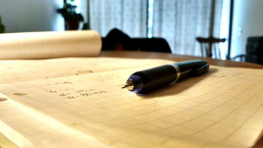 Close-up of pen and notebook on table