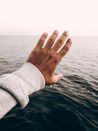 Attempt to validate nature Human Body Part Human Hand Sea Hand Water One Person Body Part Horizon Over Water Lifestyles Horizon Personal Perspective Nature Sky Land Human Limb Real People Human Finger Finger Day