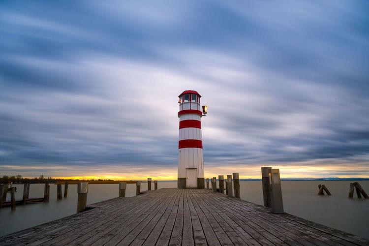 Lighthouse on pier against cloudy sky