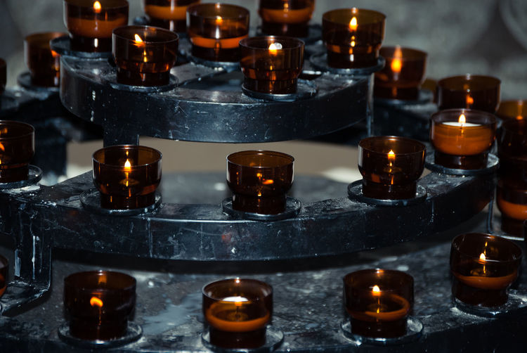 Close-up of lit tea light candles at altar in church