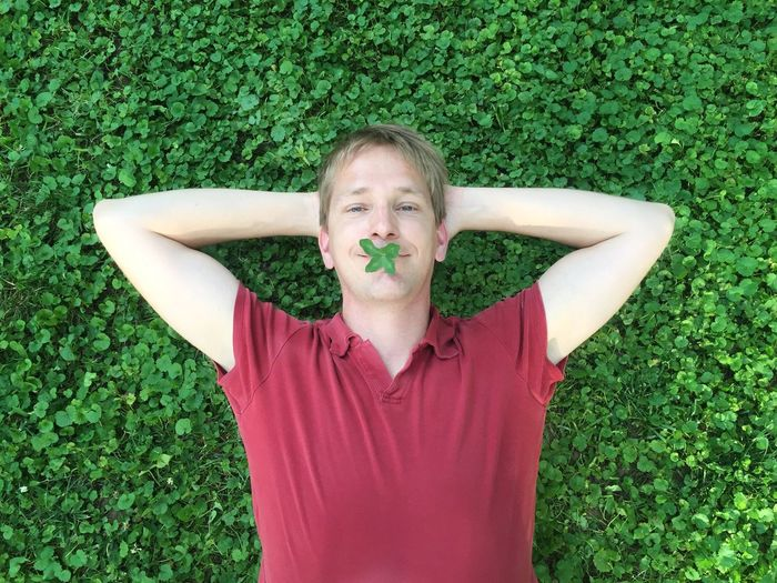 Lucky and positive Lying Down Grass Leisure Activity Plant One Person Green Color A New Beginning Relaxation Front View Nature Day Casual Clothing Portrait Outdoors Lifestyles Hands Behind Head Lying On Back