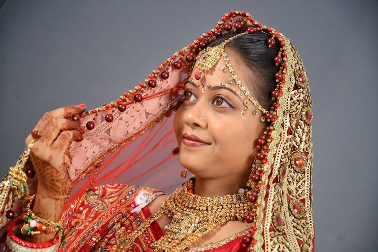 Close-up of smiling bride in traditional clothing over gray background