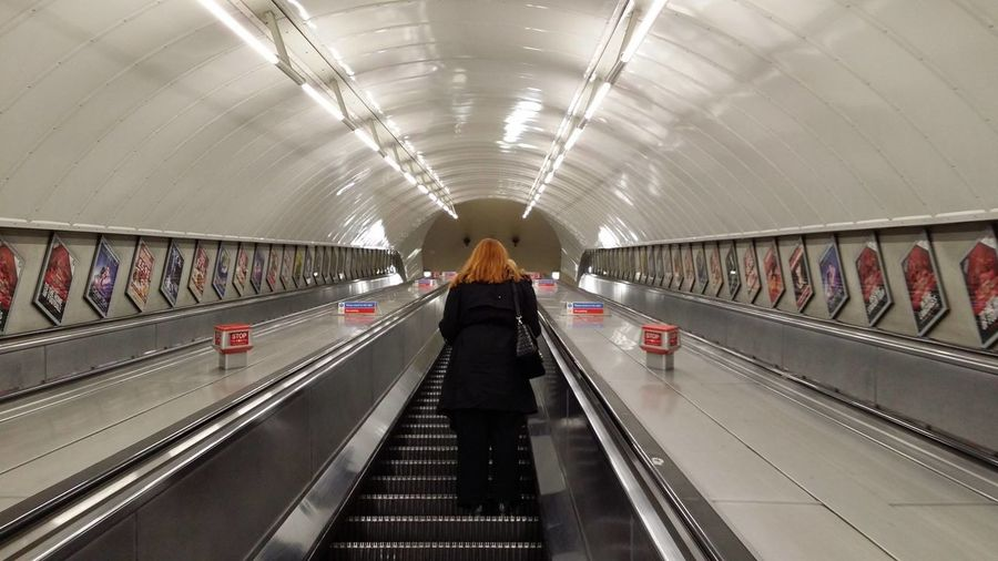 Rear View Of Woman On Escalator At London Underground