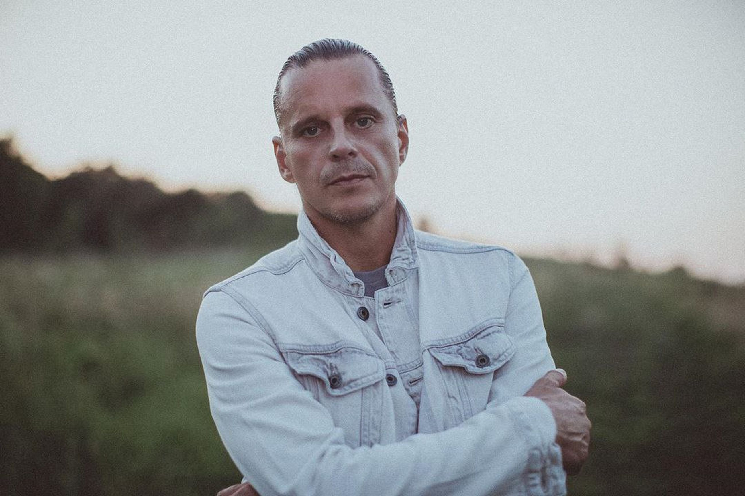 one person, portrait, adult, men, waist up, looking at camera, front view, person, standing, casual clothing, nature, senior adult, focus on foreground, day, shirt, sky, landscape, serious, rural scene, emotion, copy space, lifestyles, land, outdoors, field, button down shirt, human face, arms crossed, dress shirt, mature adult, looking, plant