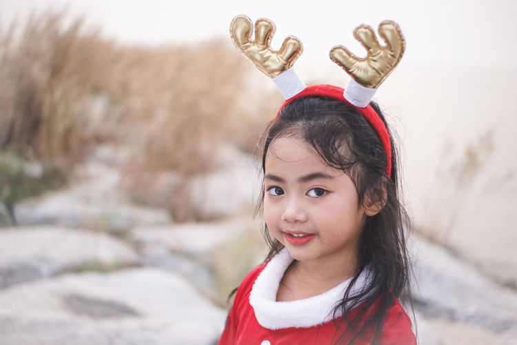 Little Santy/Reindeer on Stone dam at sea side.Little Girl in Santa Claus dress with Reindeer Headband. Santy  Santa Santa Claus Reindeer Stone Dam Sea Sea Side Thailand Winter Fashion Girl Little Girl Kid Asian  One Person Child Childhood Portrait Girls Smiling Looking At Camera Headshot Females Focus On Foreground Emotion Innocence Cute Front View Lifestyles Real People Women Warm Clothing