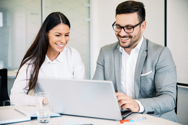 Businessman with colleague using laptop in office