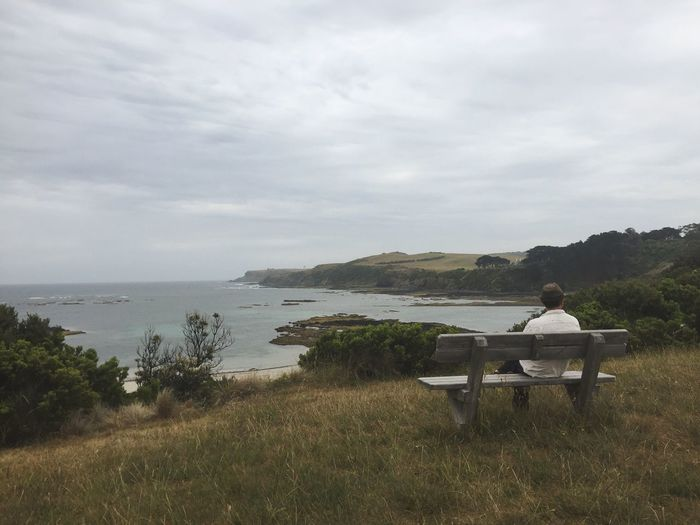Rear View Of Man Sitting On Bench At Seaside Against Cloudy Sky
