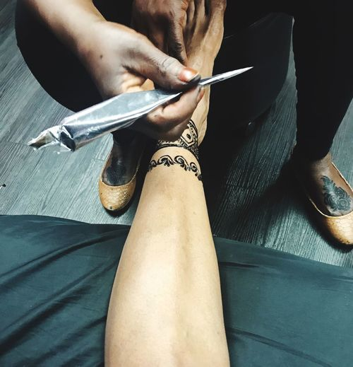 Low section of person making henna tattoo on woman leg