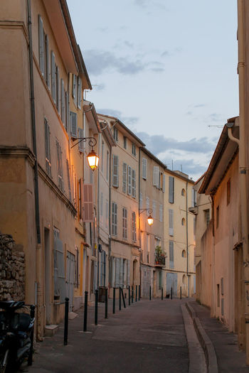 Narrow street amidst buildings against sky in city