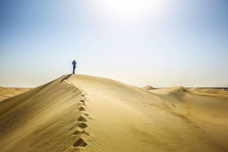 Boy photographing while standing on sand dune in desert against sky