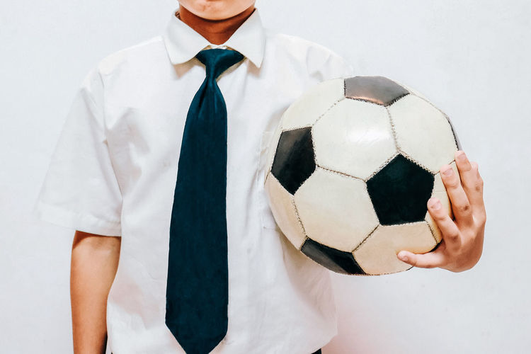 Midsection of male student holding soccer ball against white background