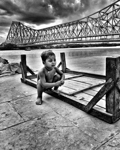 Portrait of shirtless boy sitting on bridge against sky