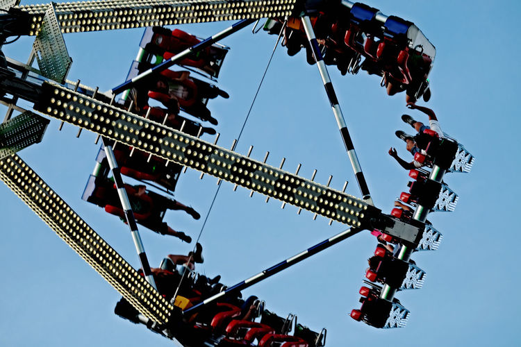 """Test of Courage on the """"Wurstmarkt"""" Amusement Park Ride Test Of Courage Blue Sky Rotation In The Air Faitgroung Fairgroundrides Rotational Energy Low Angle View Hanging Arts Culture And Entertainment Group Of People Enjoyment Leisure Activity Built Structure Motion"""