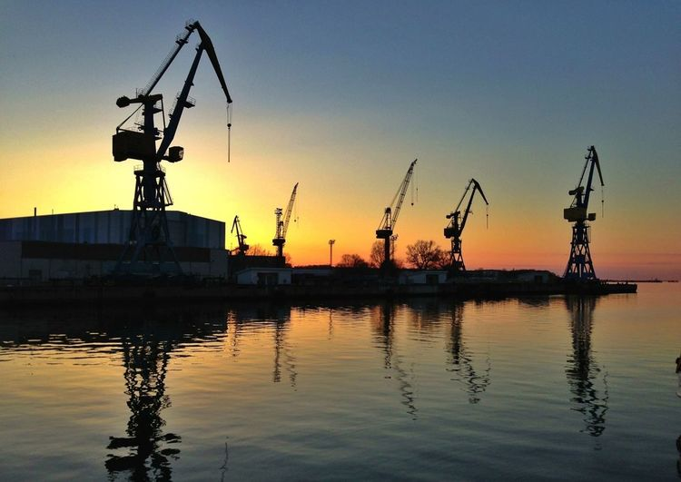 Reflection of cranes in sea during sunset