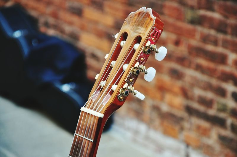 Cropped Image Of Guitar Against Brick Wall