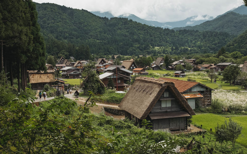 Scenic view of village by houses against sky