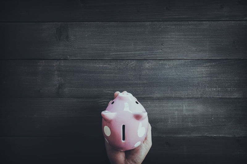 Close-up of hands holding pink piggy bank at table