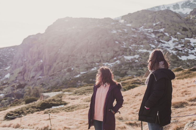 Women standing on land against mountain and sky
