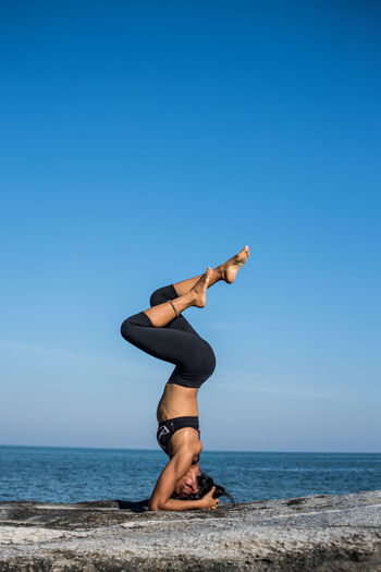 Young Woman Doing Headstand At Beach Against Sky