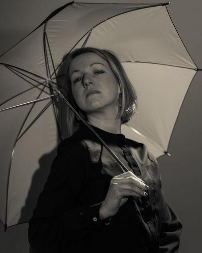 Portrait of woman under umbrella against gray background