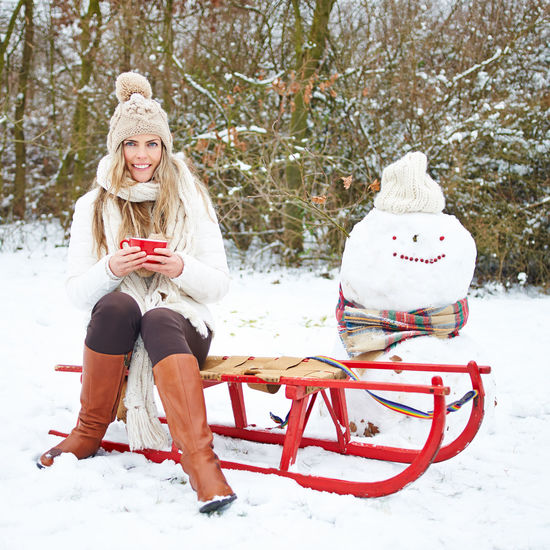Full Length Of Woman Sitting On Sled At Snow Covered Field