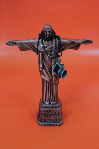 Jesus Christ Statue With Beaded Necklace And Camera On Orange Background
